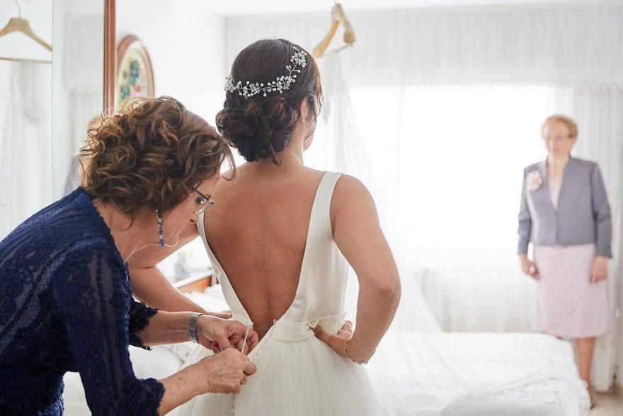 Madre ayudando a la novia a vestirse con un vestido de novia de Rosa Clará